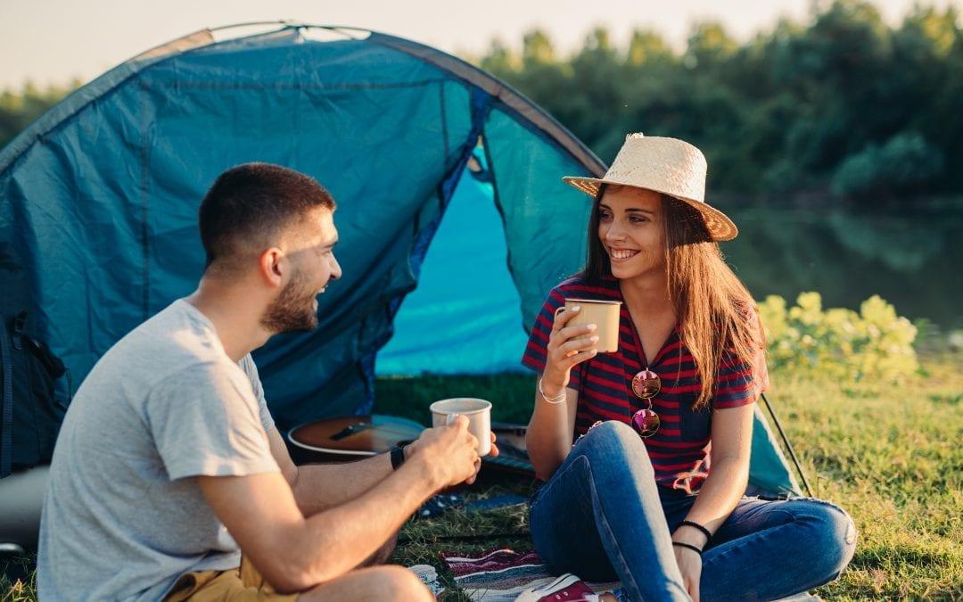 Pareja bebiendo agua filtrada en camping
